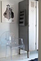 Transparent plastic Ghost chair next to vintage metal locker and below framed picture on wall
