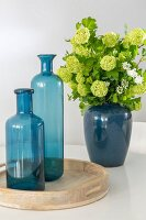 Two blue glass bottles on wooden tray and ceramic vase of lime-green hydrangeas