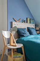 Double bed with rustic wooden headboard against blue wall, blue satin bed linen and table lamp on designer wooden chair