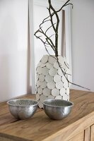 Branch in vase hand-made from preserving jar and modelling compound discs behind two bowls