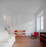White living room with colourful retro chairs and armchair