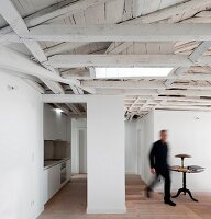 Attic with exposed, white-painted roof structure and fitted kitchen to one side