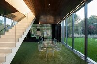 Transparent dining set on artificial lawn between staircase in contemporary house and glass wall with view of garden