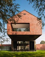 Brick house with loggia in protruding upper storey set in sunny garden