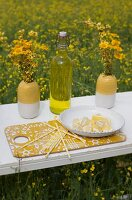 Slices of lemon on white plate and swing-top bottle between vases of dyer's chamomile on white, vintage surface in field of flowering rapeseed