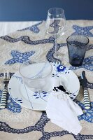 Festive place setting in blue and white on embroidered tablecloth