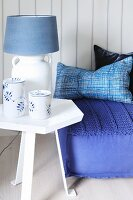 Blue and white table lamp on side table next to floor cushion