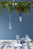 Arrangement of fir branches suspended above set table