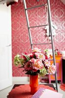Vase of flowers on doily in front of bed ladder in room with patterned wallpaper