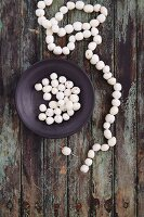 A necklace being made from snowberries