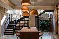 Vintner with wooden counter, bar stools, cork lampshades and steel staircase