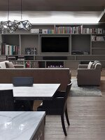 Dining area in front of lounge area with sofa set and flatscreen TV integrated into shelving system