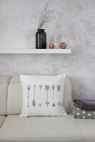 White scatter cushion with printed arrow motif on leather sofa