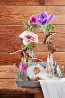 Anemones in small bottles decorated with yarn on zinc tray
