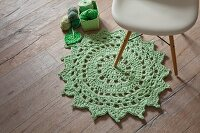 Crocheted lime-green doily-style rug on rustic wooden floor