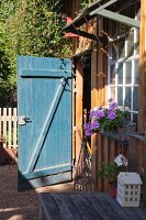 Open wood-shed door and flowering geraniums below lattice window