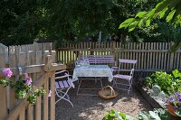 Romantic seating area in front of picket fence and deciduous trees in garden