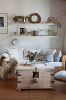 Comfortable wicker sofa below elegant floating shelves and vase of mallows on rustic trunk table