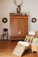 Sheepskin and scatter cushions on comfortable wicker chaise longue in front of hunting trophy above oak cabinet