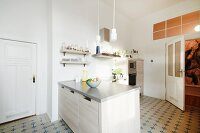 Island counter and vintage-style floor tiles in kitchen in renovated period building