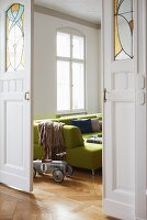 Artistic sliding doors with leaded glass panels in period apartment with green sofa