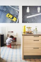 Photo artworks, traditional tiled floor and little girl playing in background in kitchen