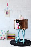 Small cabinet made from old wooden crate on top of light blue folding stool