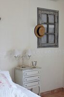 Antique bedside cabinet next to bed and straw hat hung on interior window in bedroom