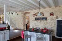 Breakfast bar in open-plan kitchen with grey and white wood-beamed ceiling and stone wall