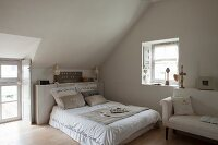Scatter cushions on double bed in bedroom with sloping ceiling