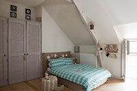 Double bed with tartan bed linen under sloping ceiling and grey wardrobe with louvre doors fitted in niche