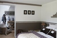 Initialled pillow covers on double bed against wall with dado painted grey-brown and view of tailors' dummy seen through open doorway