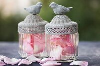 Two vintage-style glass jars with bird figurines on lids filled with pink rose petals