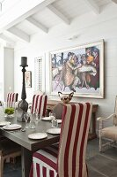 Set dining table and red and white striped loose-covered chairs in front of framed painting