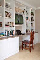Study with laptop on desk below open-fronted white shelving with TV in contemporary interior