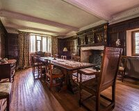 Open fireplace and wooden chairs around long dining table in grand dining room