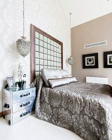 Bedspread with ornamental pattern on double bed with tall headboard against wall in corner of elegant bedroom