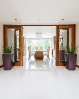 View from tiled foyer through open glass double doors flanked by planters into elegant dining area