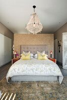 Double bed with button-tufted headboard and scatter cushions against partition and below chandelier in modern bedroom