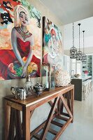 Collectors' items on wooden console table below paintings on wall: kitchen counter in background