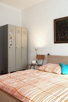 Old metal locker used as wardrobe and chair as bedside table next to double bed in bedroom