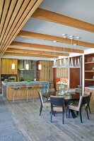 Dining area below pendant lamps in front of counter and barstools in open-plan interior