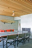 Grey canvas directors' chairs around large table below ceiling fan suspended from wooden ceiling
