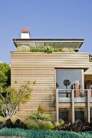 Architect-designed house clad in horizontal wooden slats with plants on roof terrace