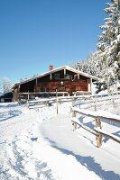 Alpine hut in snowy landscape below blue sky