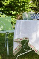 Tablecloth with hand-stitched trim on garden table