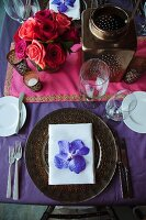 Festive place setting with orchid bloom on table set for Indian wedding