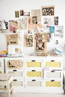 Wall decorated with clipping from retro fashion magazines above sewing utensils and sewing machine on top of white chest of drawers