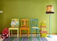Colourful wooden chairs, patchwork cushion, stack of boxes and vintage standard lamp against line green wall