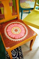 Seat of orange-painted wooden chair painted with pink and red floral motif in front of further colourful chairs